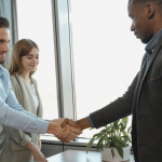 graduate student shaking hands with employer after landing a job
